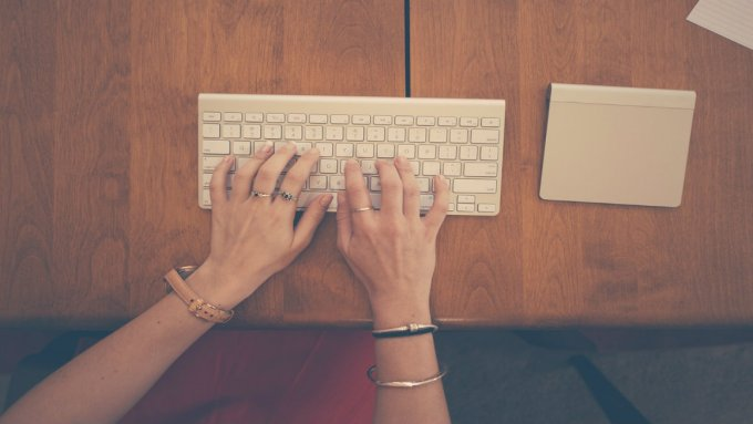 Woman's hands typing on a wireless keyboard