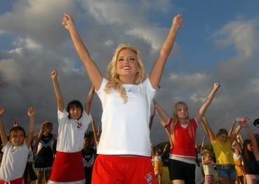 A blond female cheerleader training cheerleading students