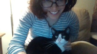 A woman smiling at the camera and petting a tuxedo-patterned cat