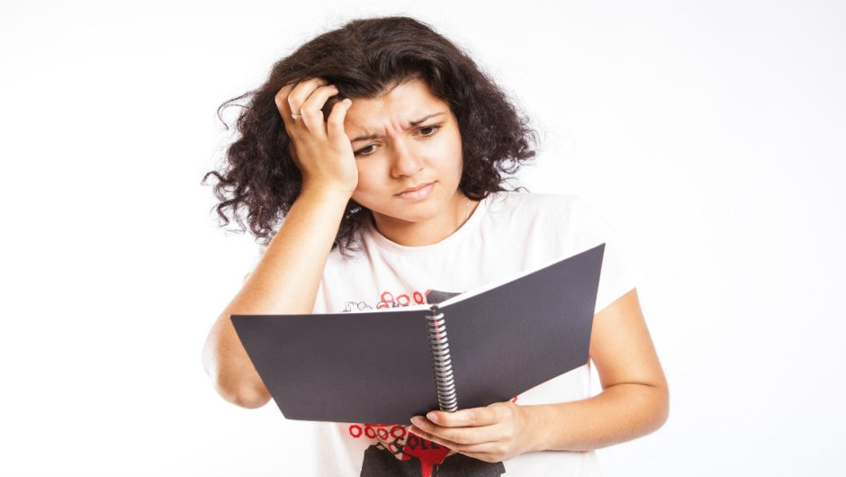 A woman staring at an open notebook and looking confused.