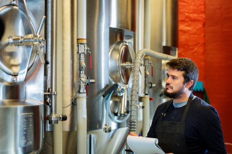 A man with a notebook standing in front of a tank of fermenting beer