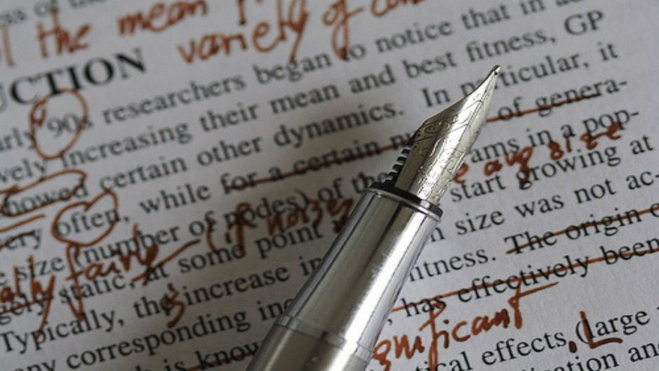 A term paper marked up in red ink with an ink pen lying on top.
